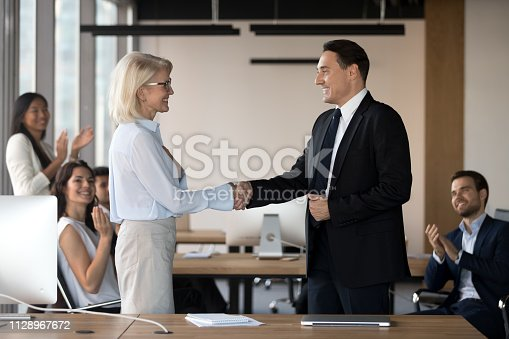 istock Executive ceo and middle aged female employee shake hands 1128967672