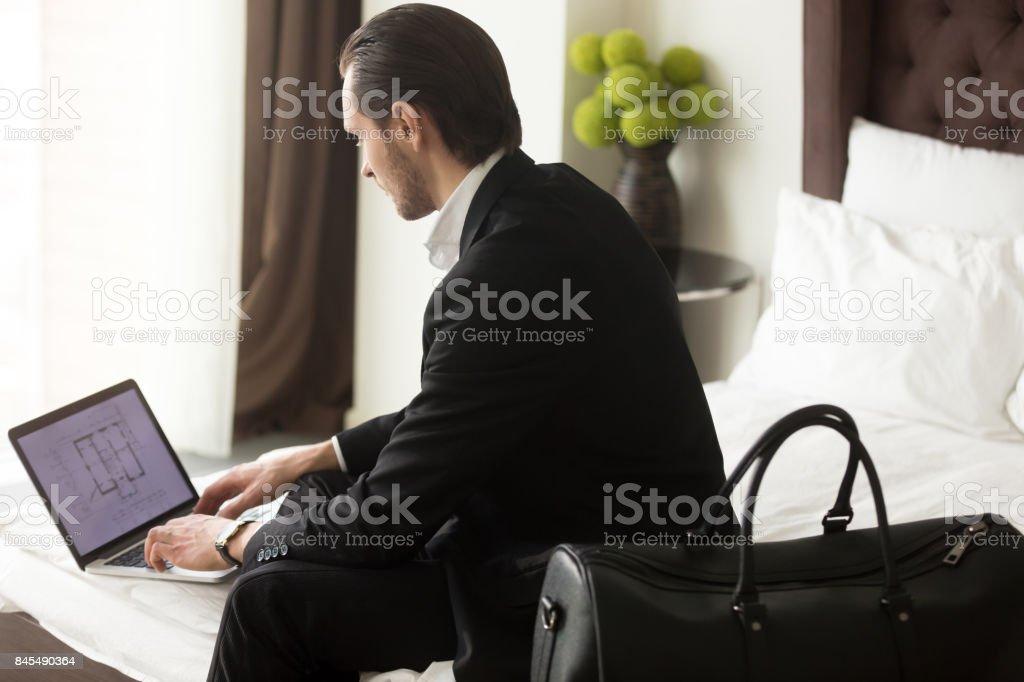 Executive checks estate plan on laptop in hotel stock photo
