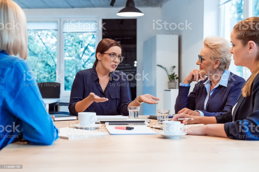 Executive discussing with colleagues in meeting Mature businesswoman discussing with colleagues. Female professionals are planning in meeting. They are sitting at board room in office. 35-39 Years Stock Photo