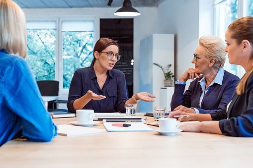 Executive Discussing With Colleagues In Meeting Stock Photo - Download Image Now