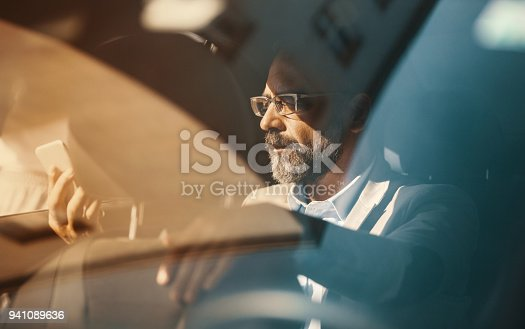 Closeup of late 40's handsome executive man driving in the back seat of a luxury limousine and using a smart phone.  Orange toned image.