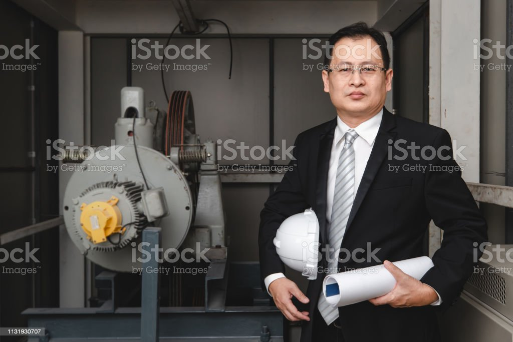 Asian executive engineer stand beside heavy machinery in industrial...