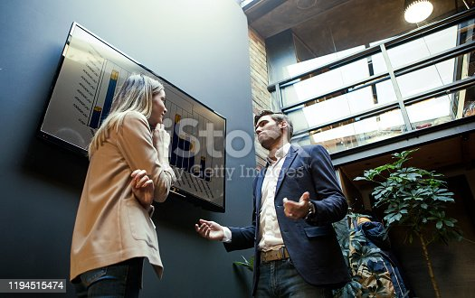 649403294 istock photo Executive giving presentation to colleague in meeting room at creative office 1194515474