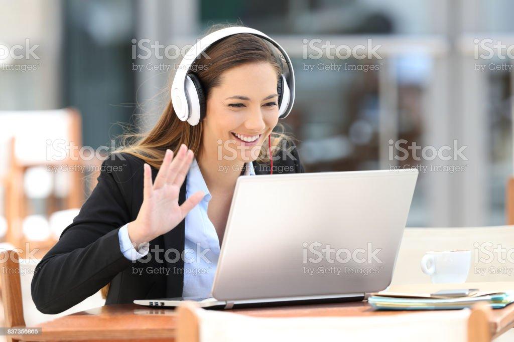Executive having a video call in a coffee shop stock photo