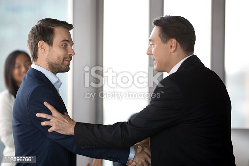 1070271598 istock photo Executive manager handshaking male employee promoting motivating worker 1128967661