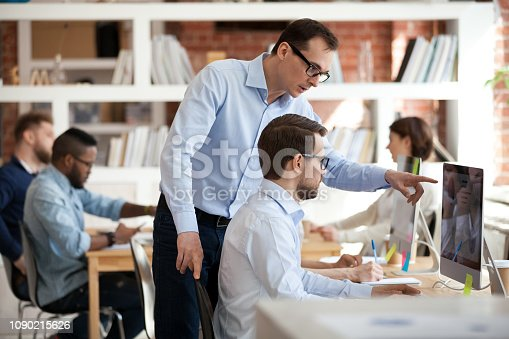 istock Executive manager helping male colleague with computer task in office 1090215626