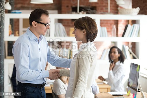 509032417 istock photo Executive manager shaking hand with young shy woman newcomer 1138949159