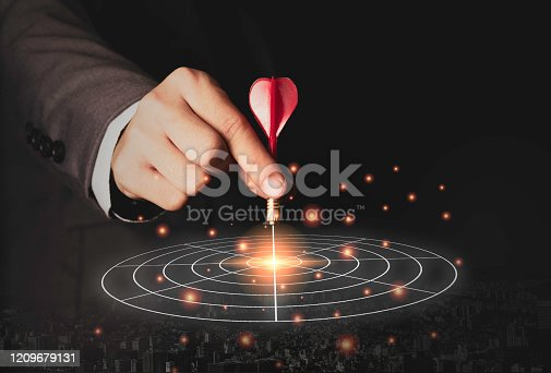 istock Executive marketing hand holding red dart put to centre of target board. Business investment goal and target concept. 1209679131