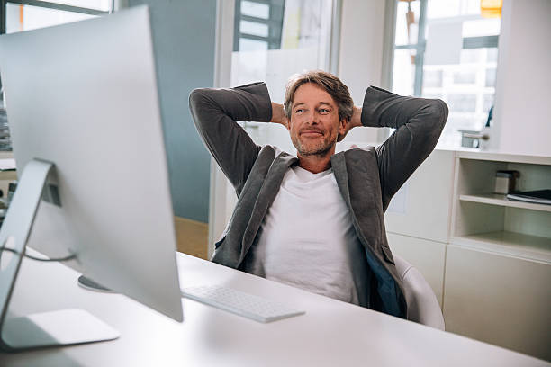 Executive mature man relaxing in office chair stock photo