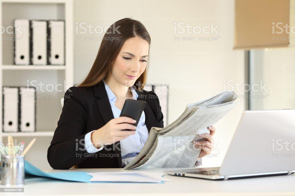 Photo de lire le journal ou lutilisation téléphone exécutif