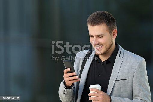 istock Executive reading phone message on the street 853843426