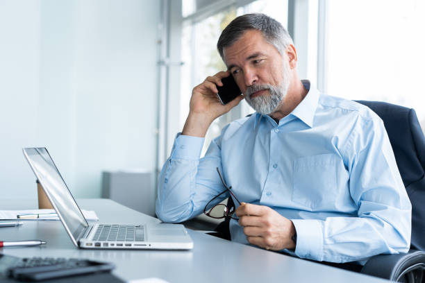 Executive senior businessman using his mobile phone and talking wih somebody while working laptop in the office. Executive senior businessman using his mobile phone and talking wih somebody while working laptop in the office serious stock pictures, royalty-free photos & images