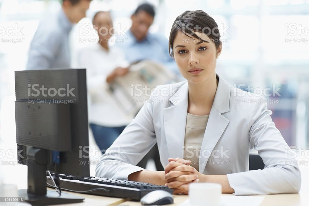 Executive sitting at desk with colleagues in the background royalty-free stock photo