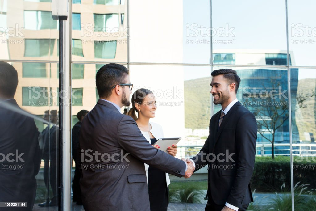 Executive team closing deal outside of building stock photo