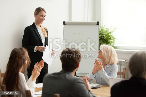 istock Executive team congratulating successful female manager with applause at meeting 924519152