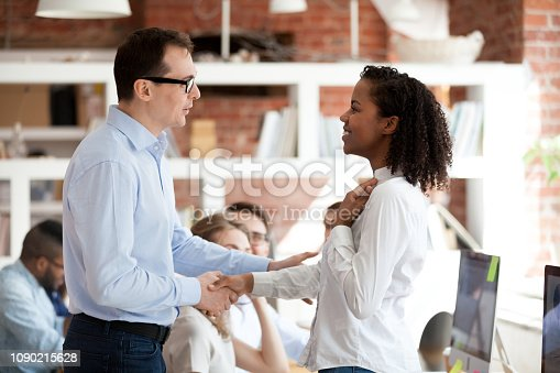 istock Executive team leader handshaking excited proud african employee, rewarding concept 1090215628