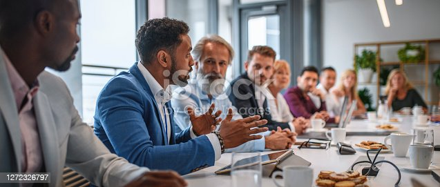 Determined African businessman expressing opinions to junior and senior colleagues on management team in conference room.