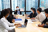 istock Executive team meeting during coronavirus or covid-19 for business new financial strategy after pandemic with all staff members wearing facial mask as of new normal and social distancing 1257417296