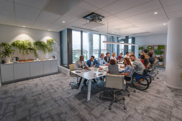 Executive Team Sitting at Conference Table in Board Room Distant view of management team sitting at conference table and talking with each other prior to start of weekly meeting. board room stock pictures, royalty-free photos & images
