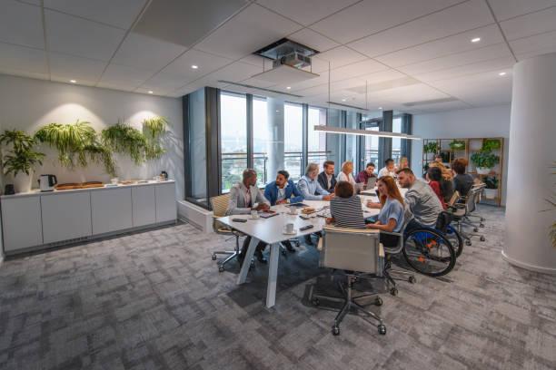 executive team sitting at conference table in board room - coinvolgimento dei dipendenti foto e immagini stock