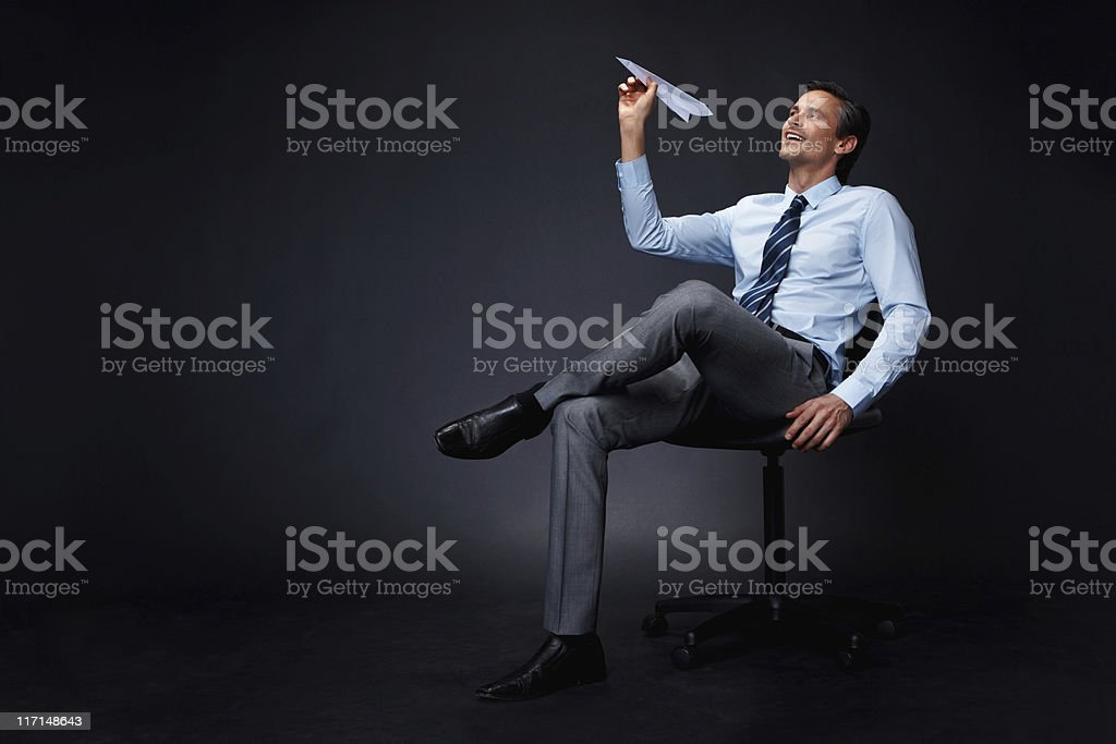 Executive throwing paper airplane stock photo
