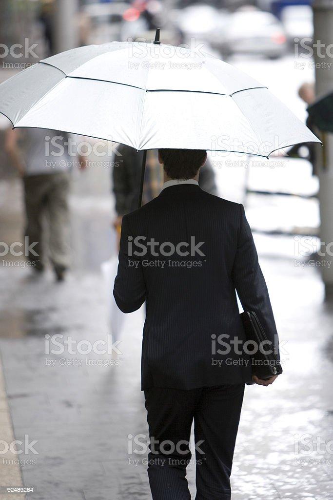 Executive walks city street in rain royalty-free stock photo