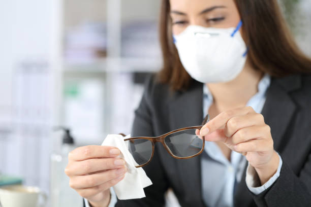 Executive wearing mask disinfecting glasses with sanitizer stock photo