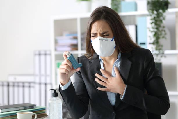 Executive trägt Maske mit Asthma halten Inhalator – Foto
