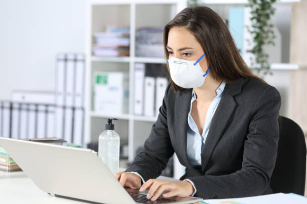 Executive wearing mask working on laptop at office stock photo