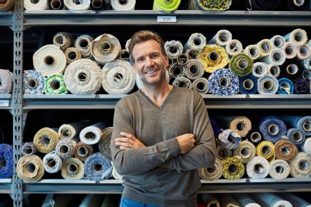 executive with arms crossed against rolled fabric - przemysł włókienniczy zdjęcia i obrazy z banku zdjęć