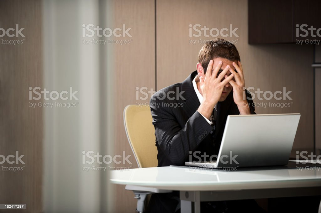 Executive with head in hands stock photo