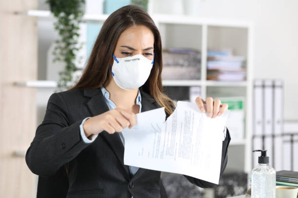 Executive with mask breaking contract at office stock photo