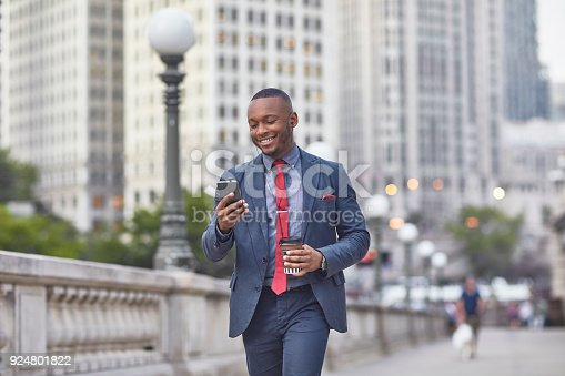 Smiling businessman holding mobile phone and disposable cup in city. Confident executive is walking against building. Professional is in suit on bridge.