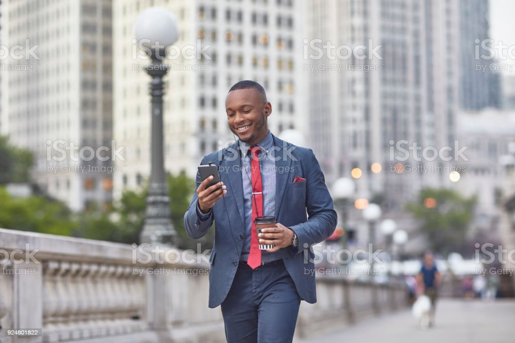 Executive with mobile phone and coffee cup in city stock photo