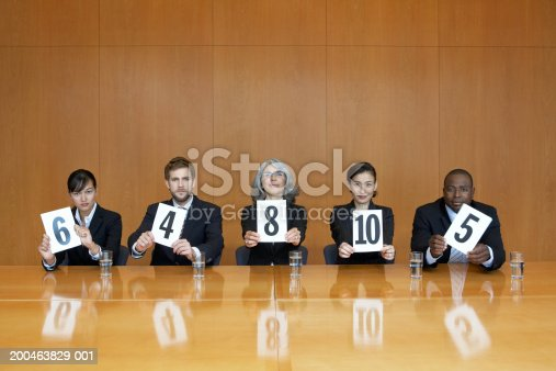 istock Executives at conference table holding score cards, portrait 200463829-001