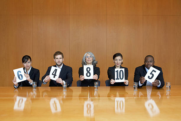 executives at conference table holding score cards, portrait - judgement stock pictures, royalty-free photos & images