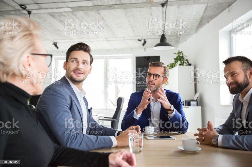 Executives brainstorming ideas Mature businessman explaining new plan to colleagues in meeting, with all men looking at senior businesswoman. Business people brainstorming idea in office meeting. Active Seniors Stock Photo
