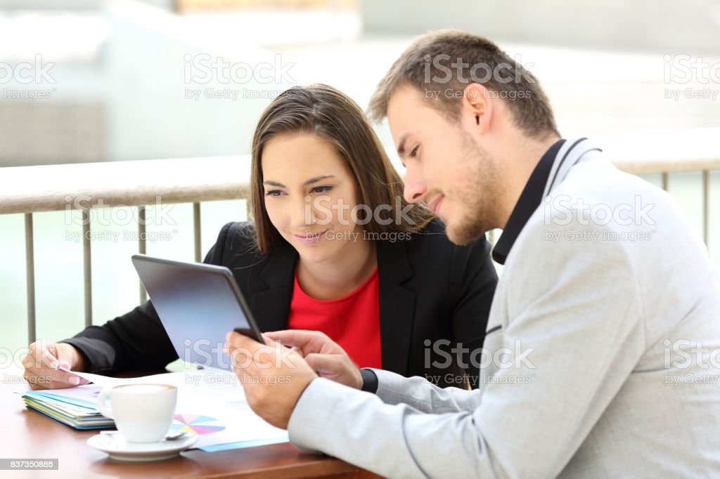 Executives consulting on line content in a coffee shop stock photo