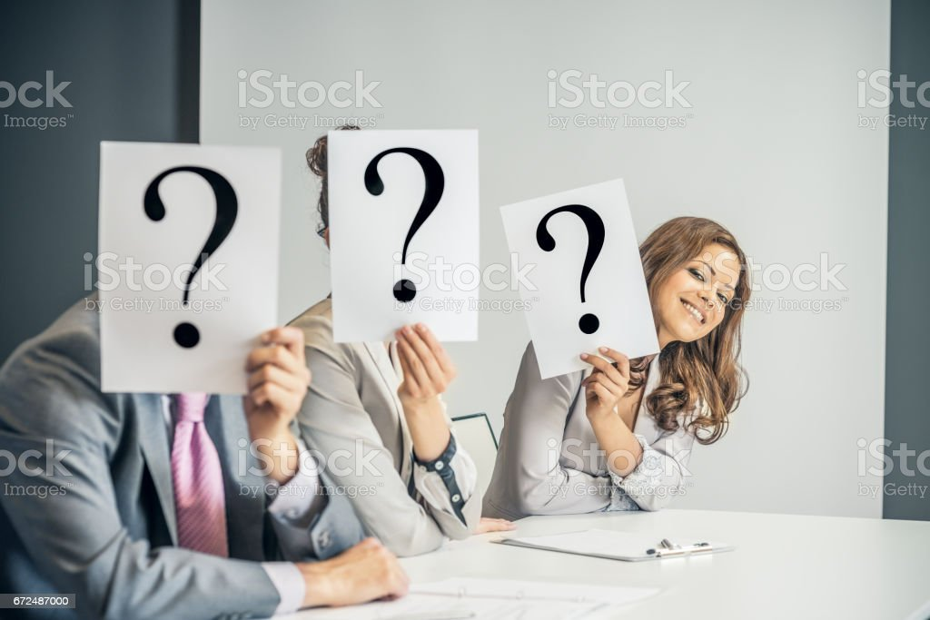 Executives covering their faces with a question mark stock photo