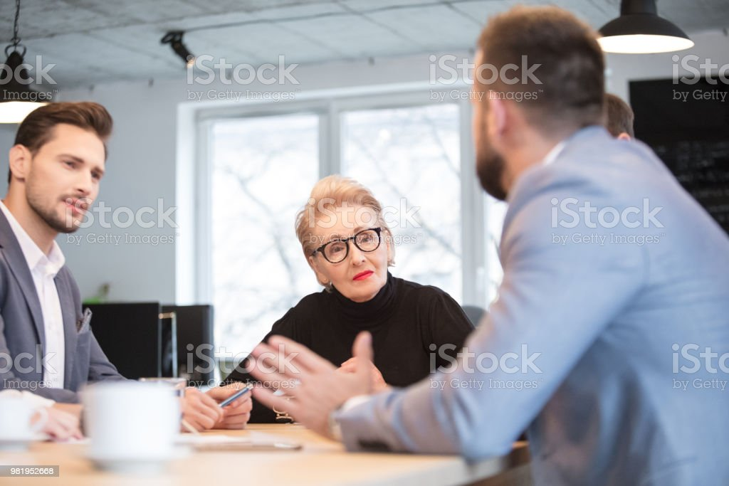 Executives discussing during a meeting in office Executives discussing during a meeting in office. Businessman and businesswoman sitting at conference table and discussing over new project. Active Seniors Stock Photo