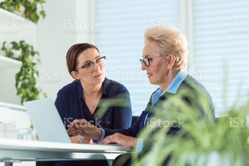 Executives discussing over new business projects Female executives discussing over new business projects. Owners are working at desk in office. Serious mature businesswoman looking at her role model. 40-44 Years Stock Photo