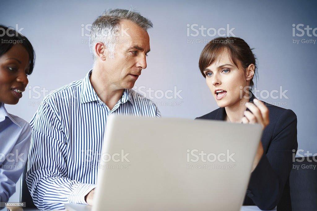 Executives discussing proposal Team of executives conversing while viewing laptop Active Seniors Stock Photo