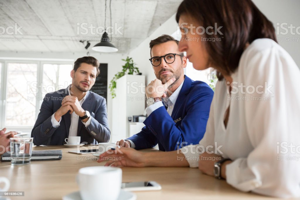 Executives during boardroom meeting Mature businessman listening to female colleague during office meeting. Group of business executives discussing new plans in meeting. Adult Stock Photo