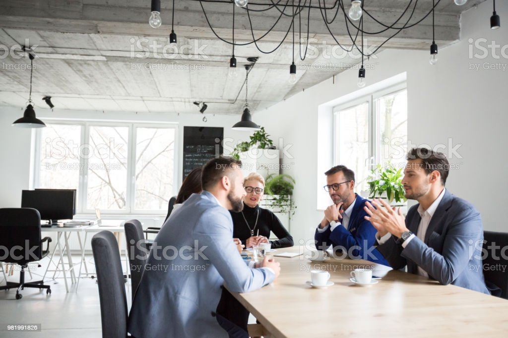 Executives having a meeting in office Young businessman explaining strategy to colleagues in meeting. Business people brainstorming idea in office meeting. Active Seniors Stock Photo