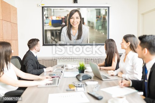 istock Executives Looking At Blank Projection Screen In Meeting 1056871234