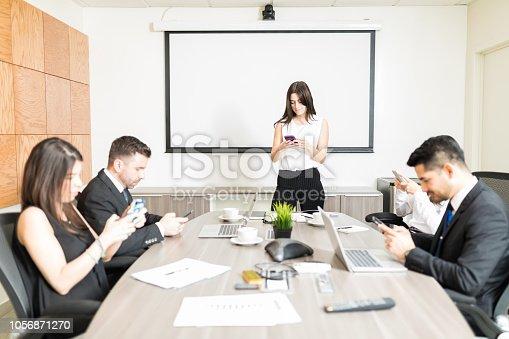 Multiethnic business people messaging on smartphones in boardroom