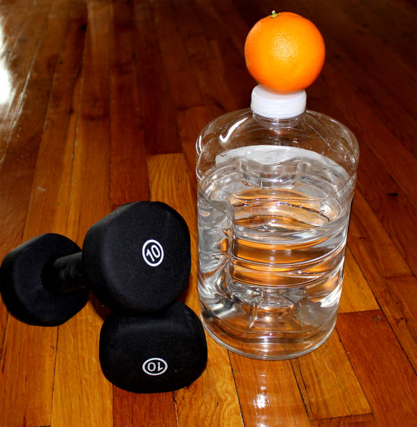 Exercise barbells on the floor next to bottle of water with orange on top. stock photo