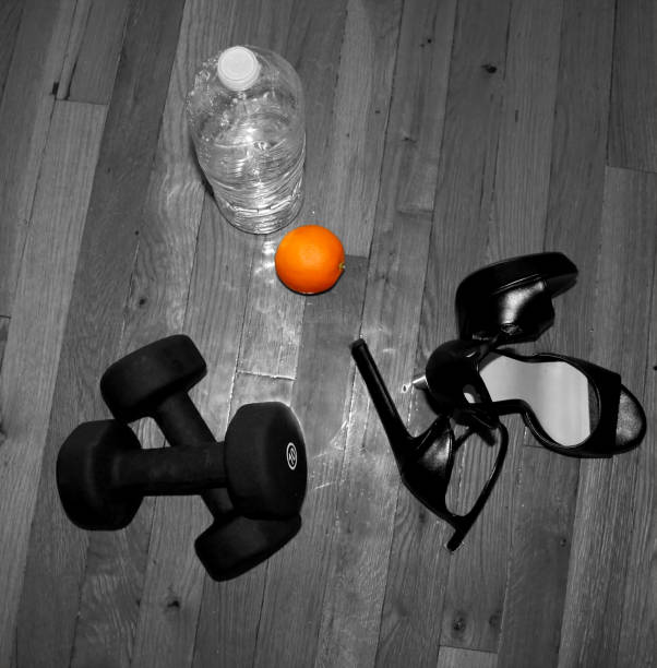 Exercise barbells on the wooden floor next to large bottle of water with orange on top and high hills nearby. stock photo