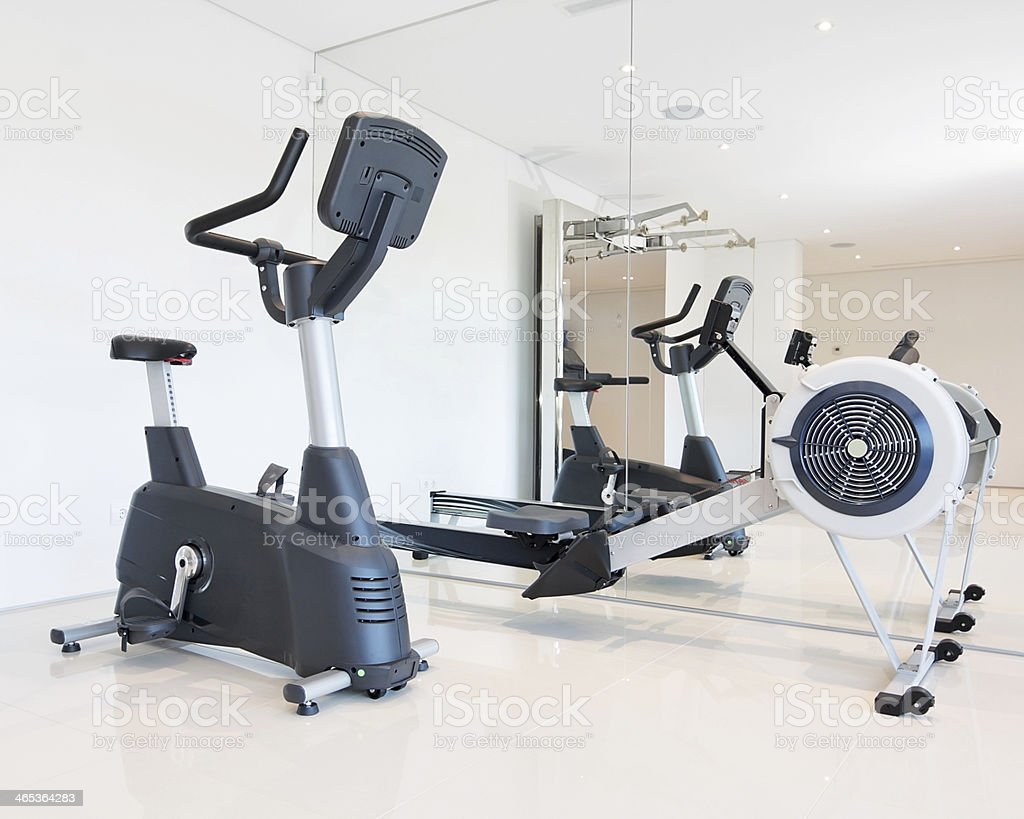 Exercise bike and rowing simulator in the luxury gym close-up. stock photo