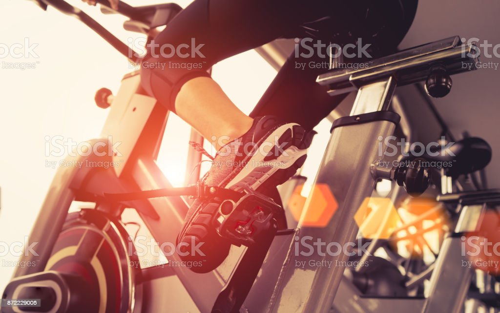 Exercise bike cardio workout at fitness gym of woman taking weight loss with machine aerobic for slim and firm healthy in the morning. stock photo